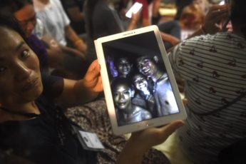 "A family member shows a picture of four of the twelve missing boys near the Tham Luang cave at the Khun Nam Nang Non Forest Park in Mae Sai on July 2, 2018. Twelve boys and their football coach trapped in a flooded Thai cave for nine days were ""found safe"" on late July 2, in a miracle rescue after days of painstaking searching by divers. / AFP PHOTO / LILLIAN SUWANRUMPHA / CORRECTION: ìThe erroneous mention[s] appearing in the metadata of this photo by LILLIAN SUWANRUMPHA                  has been modified in AFP systems in the following manner: [A family member shows a picture of four of the twelve missing boys near the Tham Luang cave at the Khun Nam Nang Non Forest Park in Mae Sai on July 2, 2018.] instead of [A happy family member shows the latest pictures of the missing boys taken by rescue divers inside Tham Luang cave when all members of children's football team and their coach were found alive in the cave at  Khun Nam Nang Non Forest Park in the Mae Sai district of Chiang Rai province late July 2, 2018]. Please immediately remove the erroneous mention[s] from all your online services and delete it (them) from your servers. If you have been authorized by AFP to distribute it (them) to third parties, please ensure that the same actions are carried out by them. Failure to promptly comply with these instructions will entail liability on your part for any continued or post notification usage. Therefore we thank you very much for all your attention and prompt action. We are sorry for the inconvenience this notification may cause and remain at your disposal for any further information you may require.î"