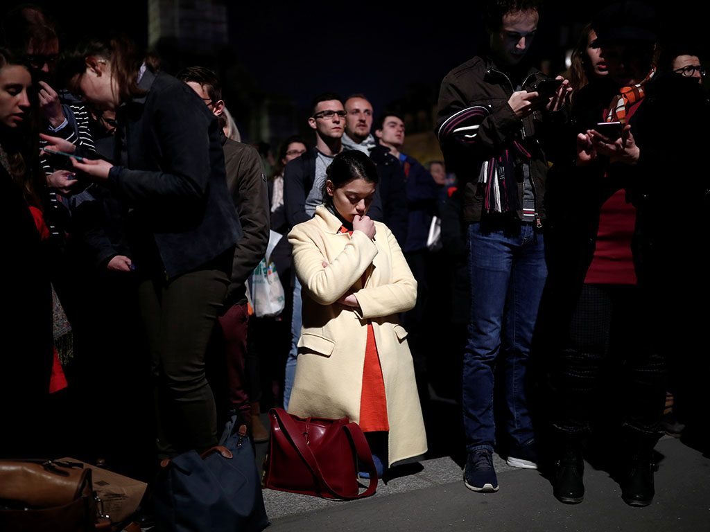 A woman prays next to Notre Dame Cathedral after it suffered heavy damage from a fire, in Paris, France April 15, 2019. REUTERS/Benoit Tessier - RC1A12380020